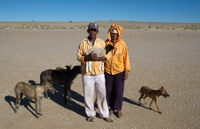 Koopan, Northern Cape, Willem and Siina Jakobs carry a lamb that they found on their farm at Andriesvale back to their neighbours at Koopan. The couple were startled when I commented that they were good neighbours, honesty and generosity of time seem to be part of the culture that enables people to survive the extreme climate of the arid Kalahari. On giving the Jacobs a lift, I offered to put the dogs on the back of the bakkie, but Willem insisted they would run behind the vehicle. It rahe rfelt like being chased by the hounds of hell, given the tempretures on the surface of Koopan. Greg Marinovich / Storytaxi.